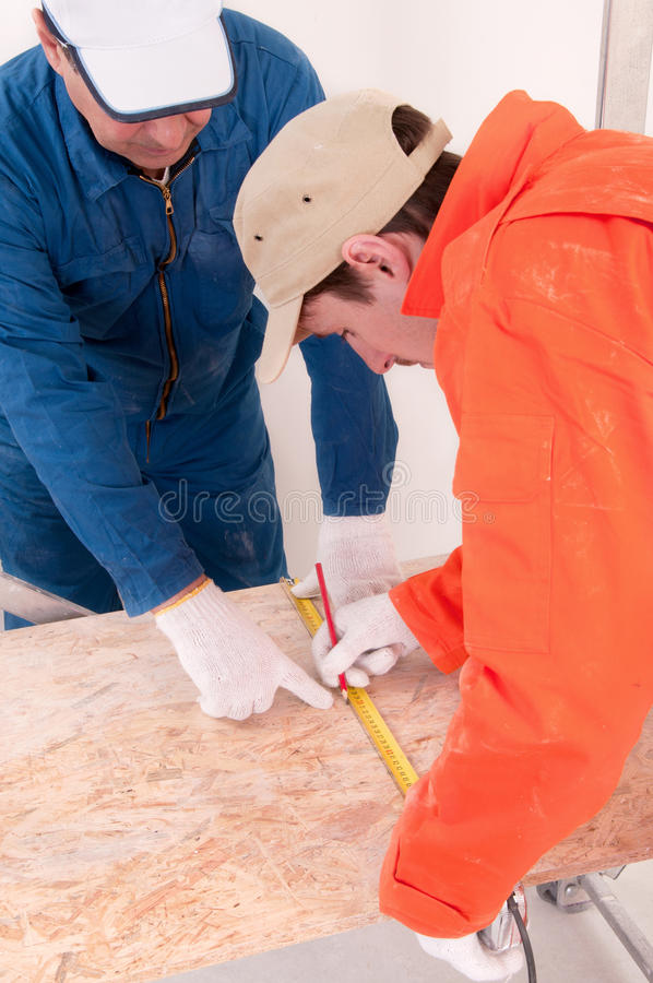 Construction worker doing measuring. Two construction worker doing measuring royalty free stock photography