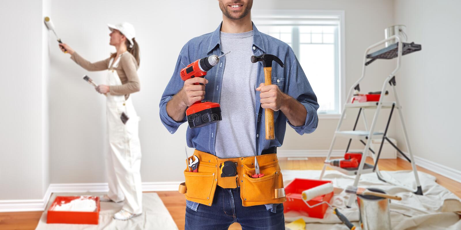 Construction worker with drill and hammer stock images