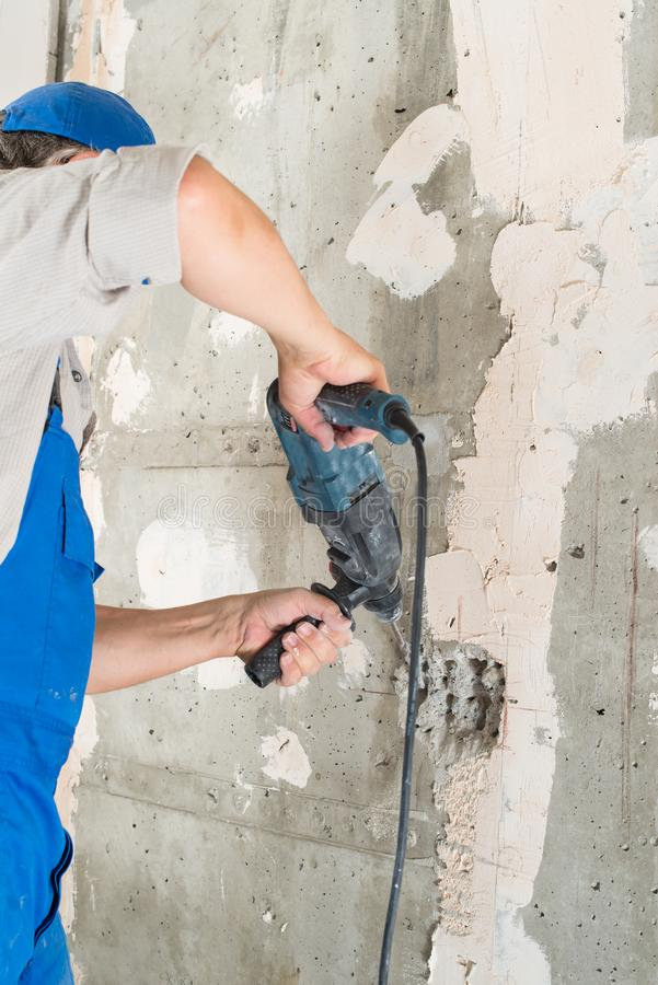 Construction worker drilling hole. Repair in house royalty free stock photography