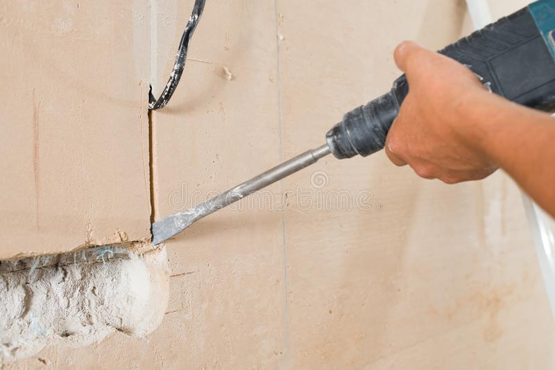 Construction worker drilling hole. Repair in house royalty free stock photo
