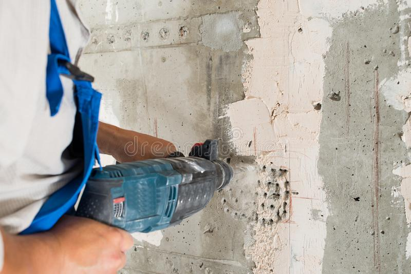 Construction worker drilling hole. Repair in house stock photos