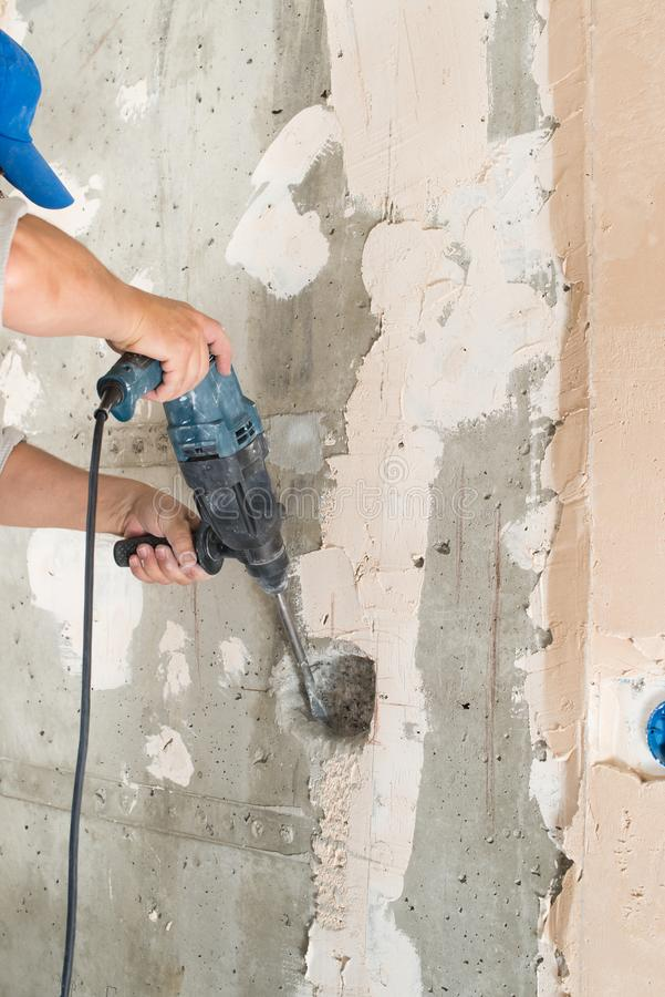 Construction worker drilling hole. Repair in house stock image