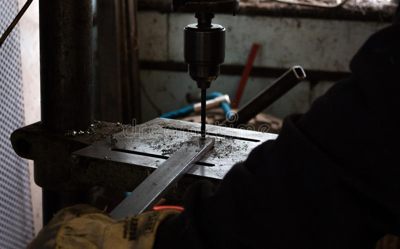 Construction worker drills hole in rod of metal iron using industrial drill. In a dark workshop / workshed / factory royalty free stock photography