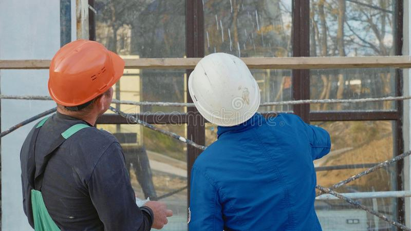 Construction worker and engineer talking at construction site site, rear view. stock images