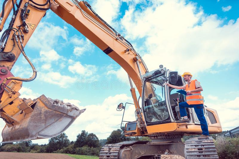 Construction worker on excavator planning the work to be done stock photos