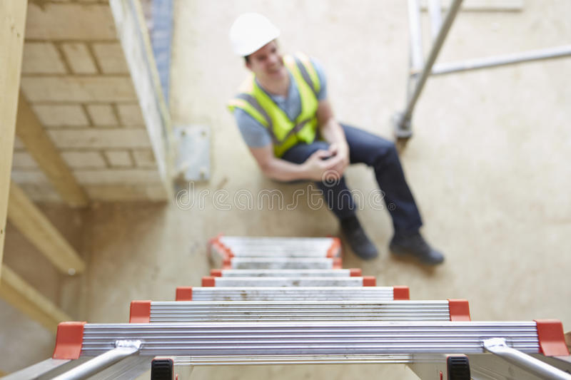 Construction Worker Falling Off Ladder And Injuring Leg royalty free stock photography