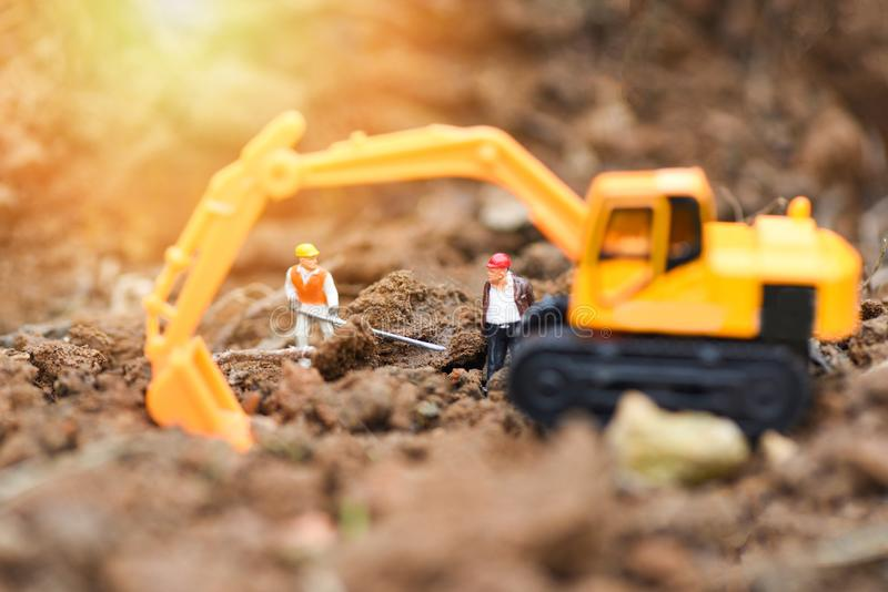 Construction worker figurines working digging ground soil with Backhoe excavator stock photography