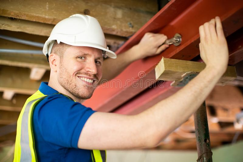 Construction Worker Fitting Steel Support Beam Into Renovated House Ceiling royalty free stock images