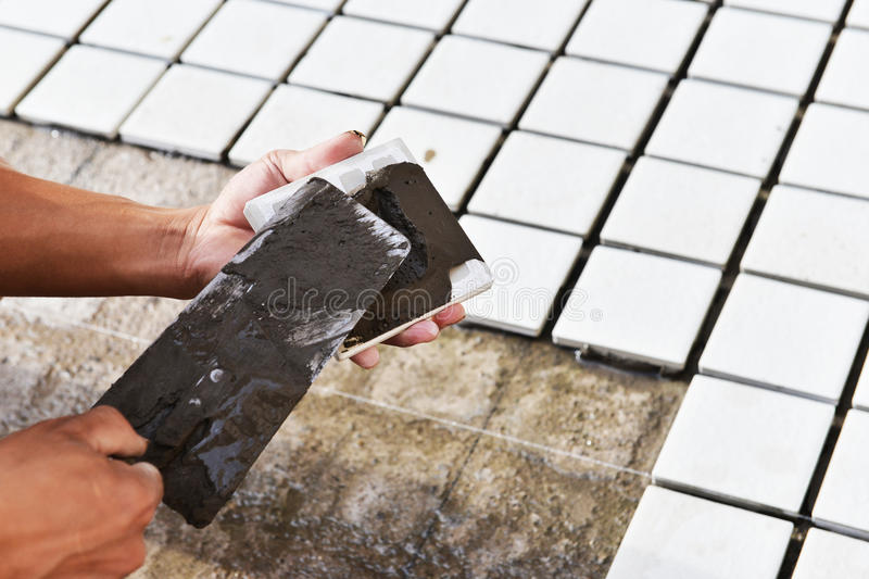 Construction worker glued ceramic tile royalty free stock photo