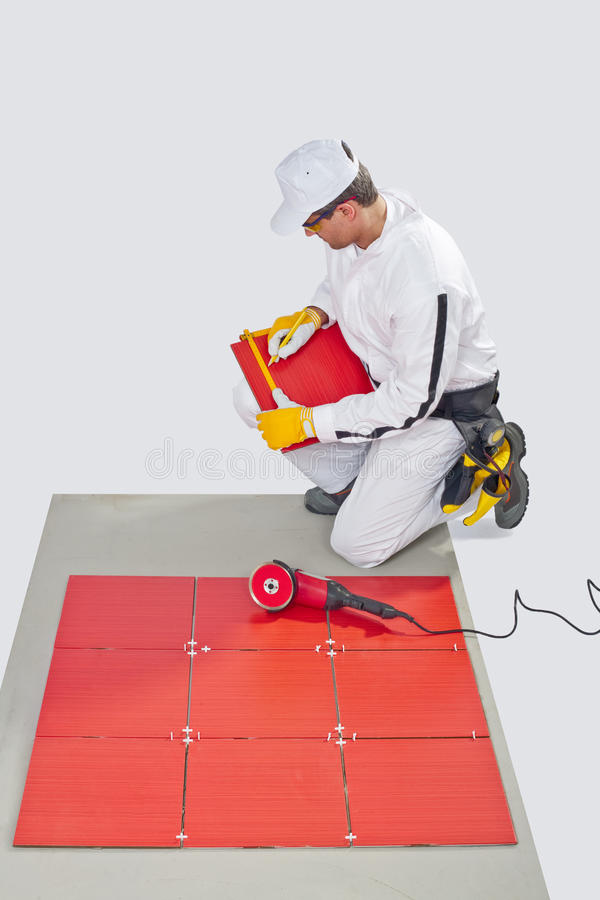 Construction worker glued red ceramic tile royalty free stock images