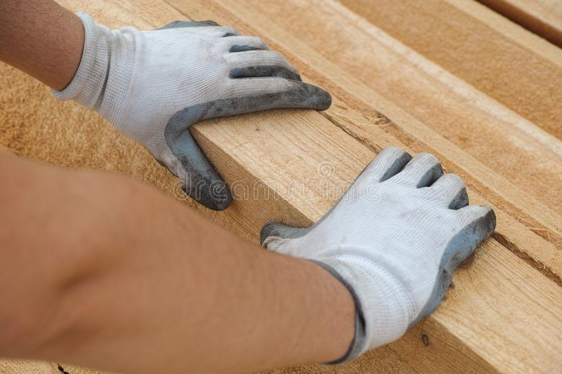 Construction worker grabbing plank of wood. Close up royalty free stock photography