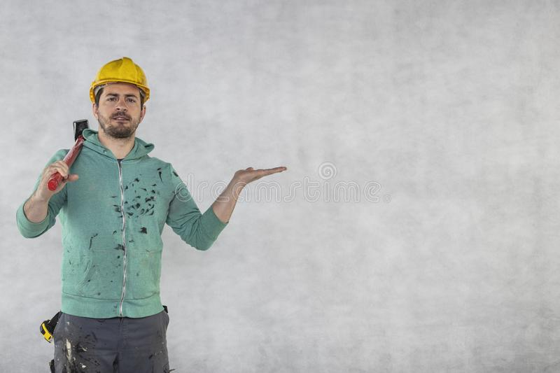 Construction worker with a hammer in hand, concept of construction and disassembly, renovation royalty free stock image