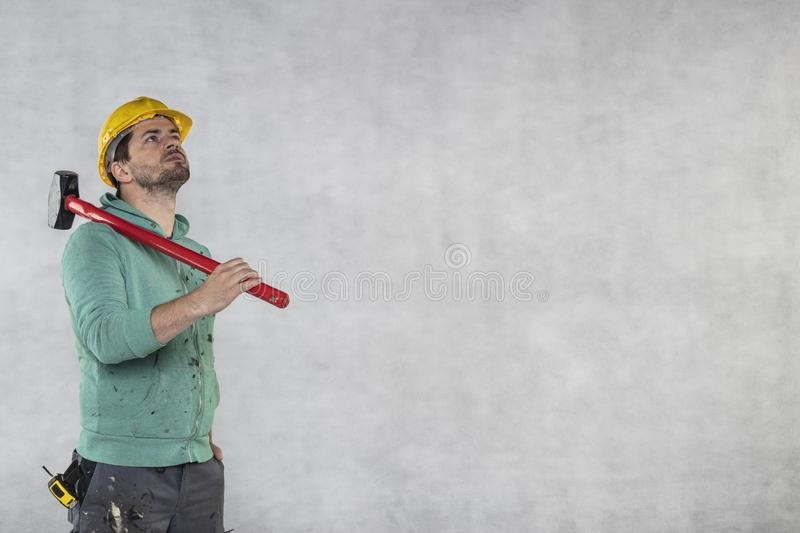 Construction worker with a hammer in hand, concept of construction and disassembly, renovation royalty free stock photography