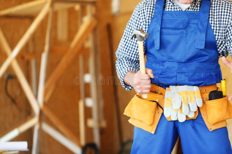 Construction worker with hammer. Construction worker in tool belt with hammer at construction site stock photo