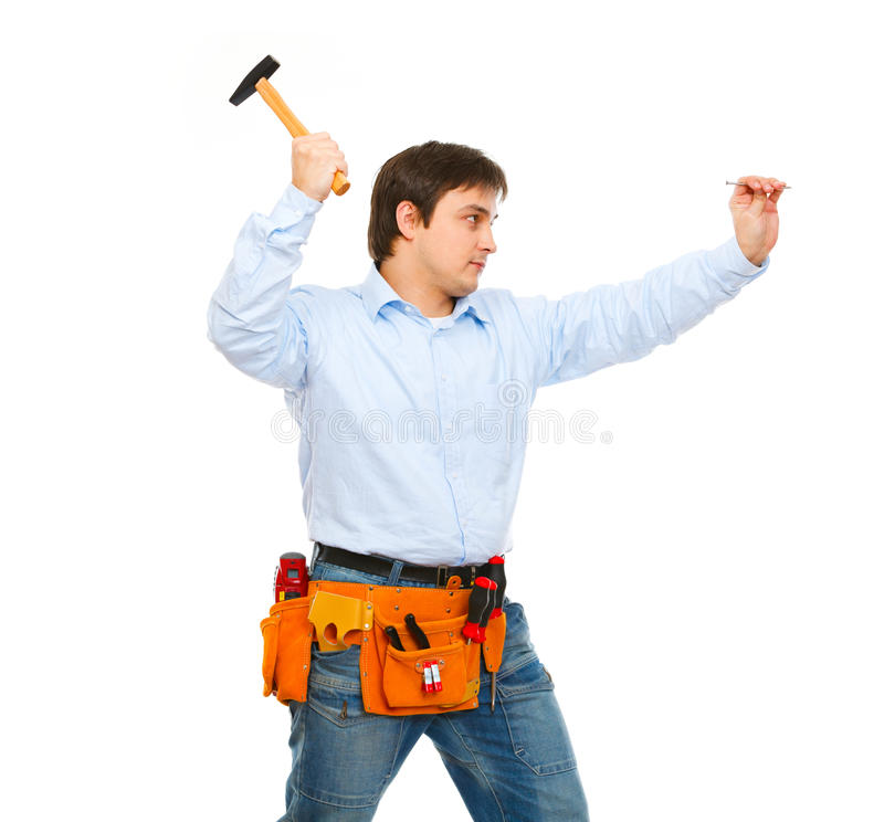 Construction worker hammering nail stock photography
