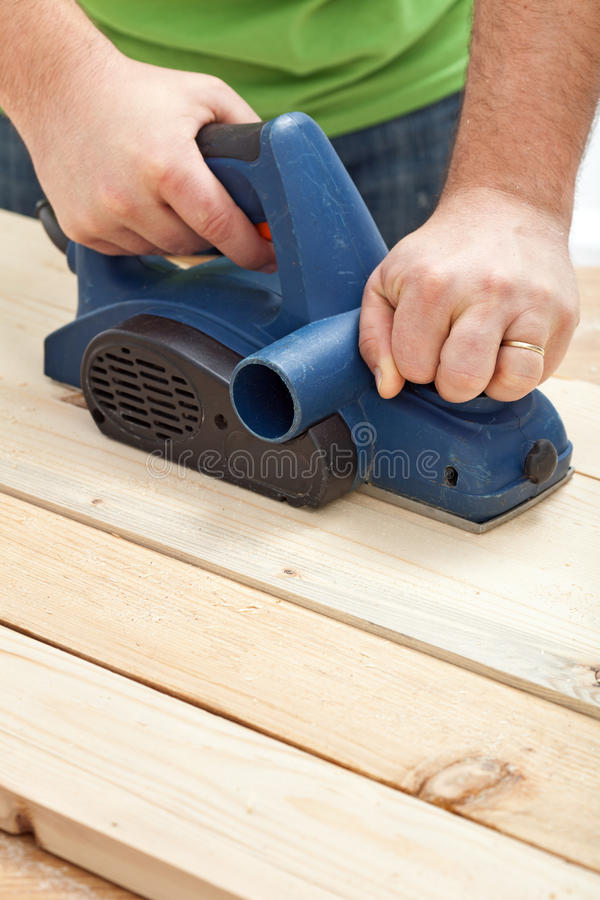 Construction worker hands with electric planer royalty free stock images