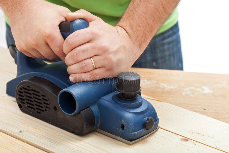 Construction worker hands and power tool. Planing a piece of wood stock photo