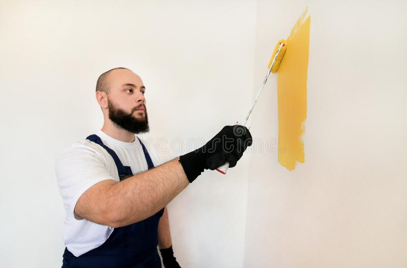 Construction worker and painter using paint roller brush painting of wall with yellow color. stock photo