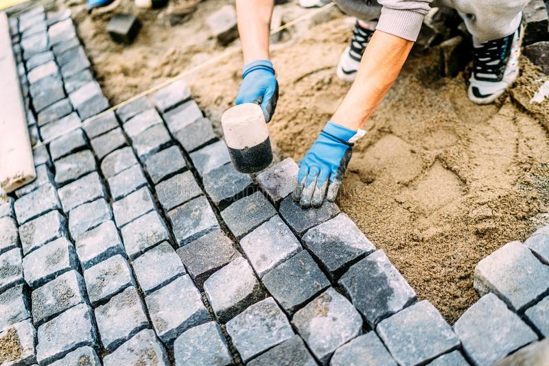 construction worker, handyman using cobblestone granite stones for creating walking path. Terrace or sidewalk details stock photo