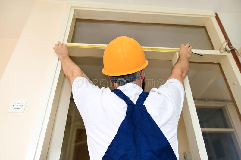 Construction worker and handyman is working on renovation of apartment. Builder is measuring of room door using measure tape. Construction worker and handyman royalty free stock photography