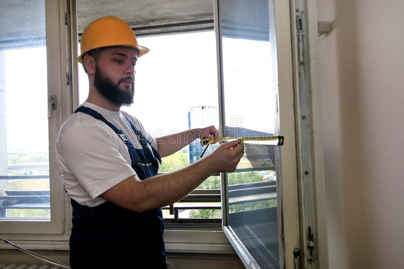 Construction worker and handyman is working on renovation of apartment. Builder is measuring window using measure tape. stock photography
