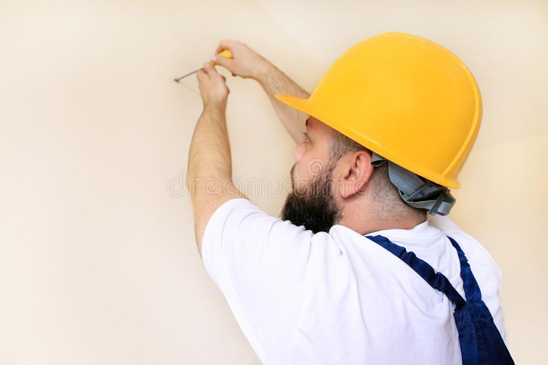 Construction worker and handyman works on renovation of apartment. Builder using yellow screwdriver screws steel screw out of wall stock images