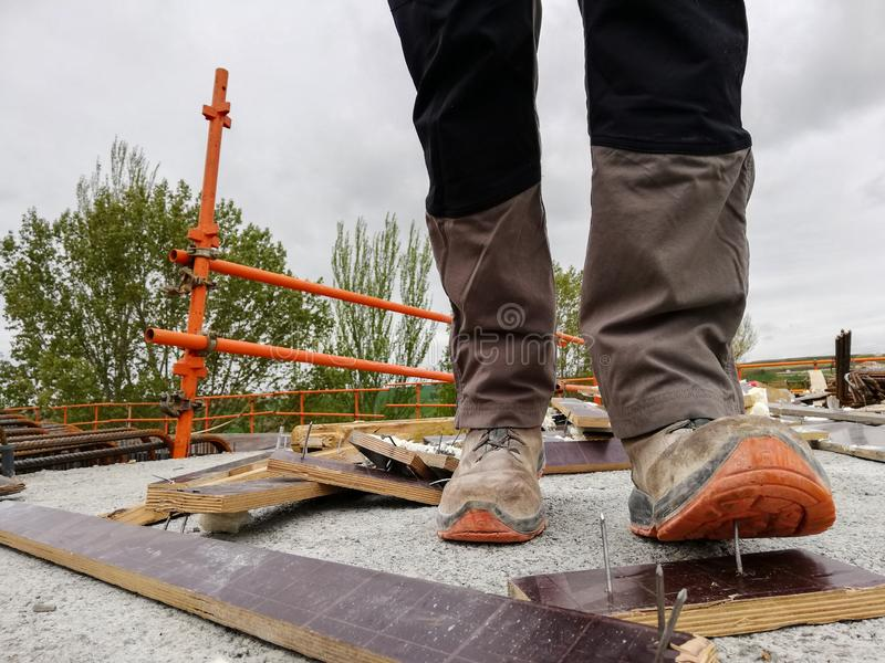 A construction worker has an accident while walks through a site with debris and stepping on a nail stock photography