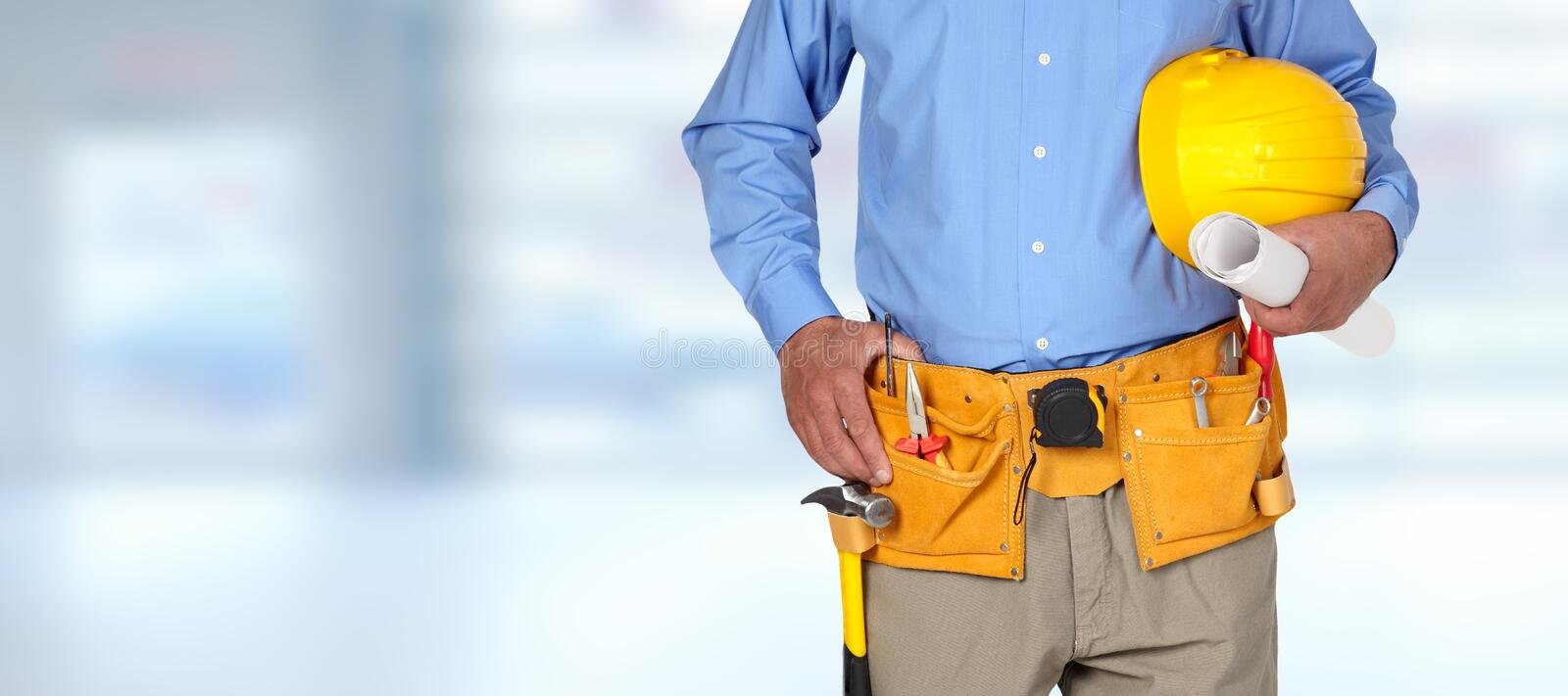 Construction worker with helmet and tool belt. royalty free stock photography