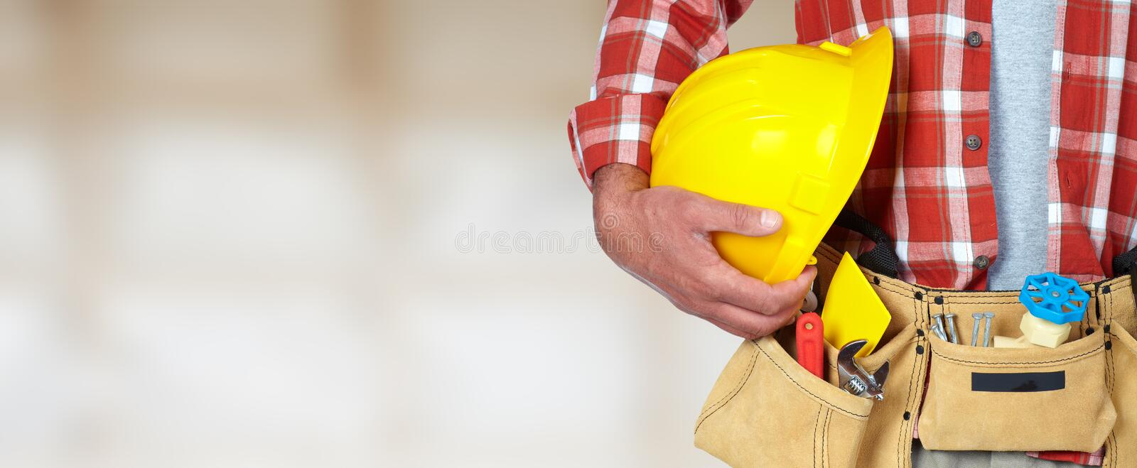 Construction worker with helmet and tool belt. royalty free stock image