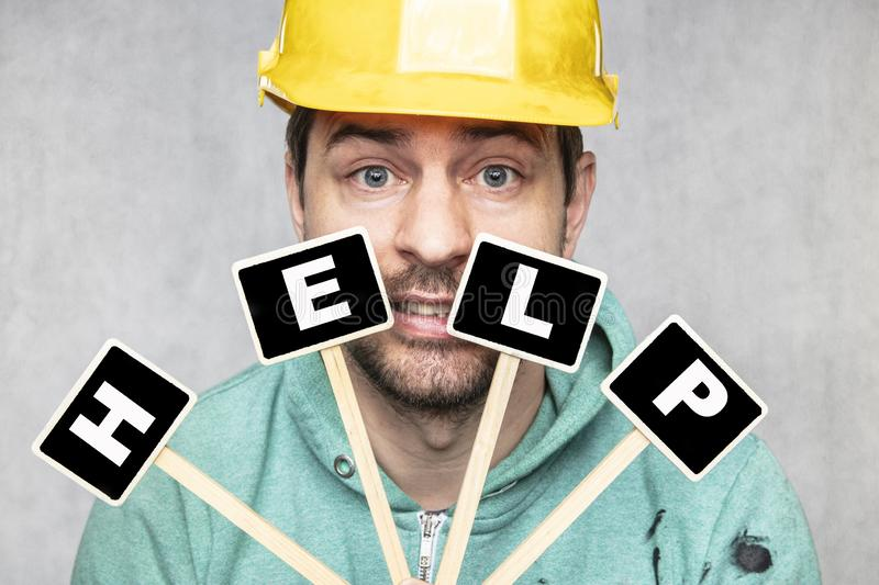 Construction worker holding a blackboard with space for text or text, copy space royalty free stock image