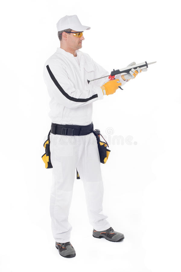 Construction worker holding a gun silicone sealant royalty free stock photos