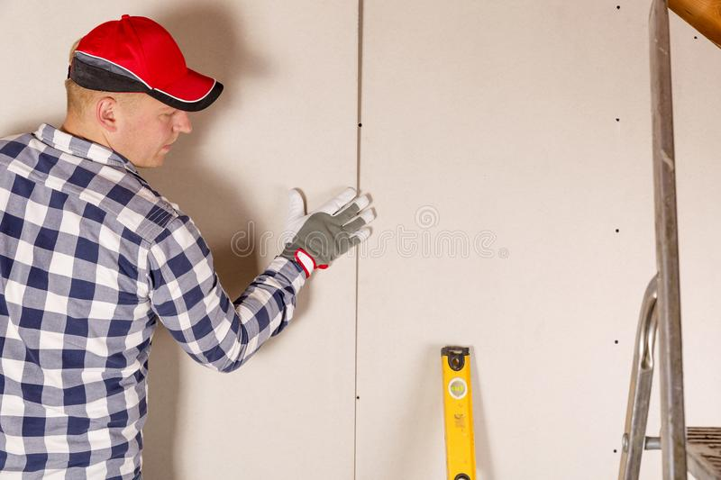 Construction worker holding gypsum board. Attic renovation. Inst. Allation of drywall royalty free stock photos