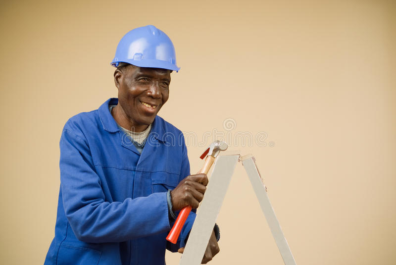Construction Worker Holding Hammer On Ladder Stock Image