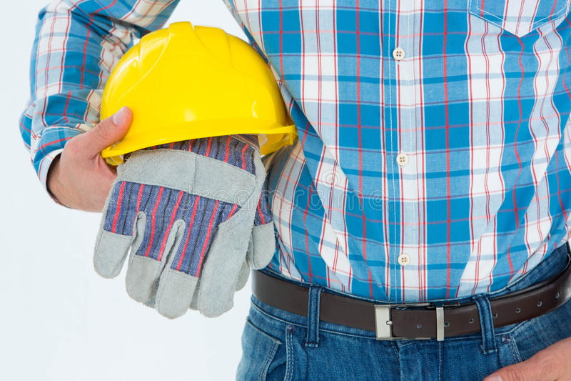 Construction worker holding hard hat and gloves stock photos
