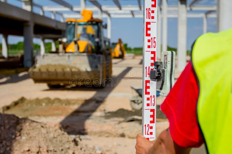 Worker is holding leveling rod to measuring level on construction site royalty free stock images