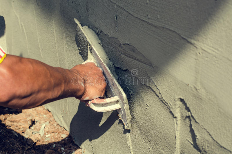 Construction worker holding plastering trowel smoothing wall defects. Construction worker hand holding plastering trowel smoothing wall defects royalty free stock photo