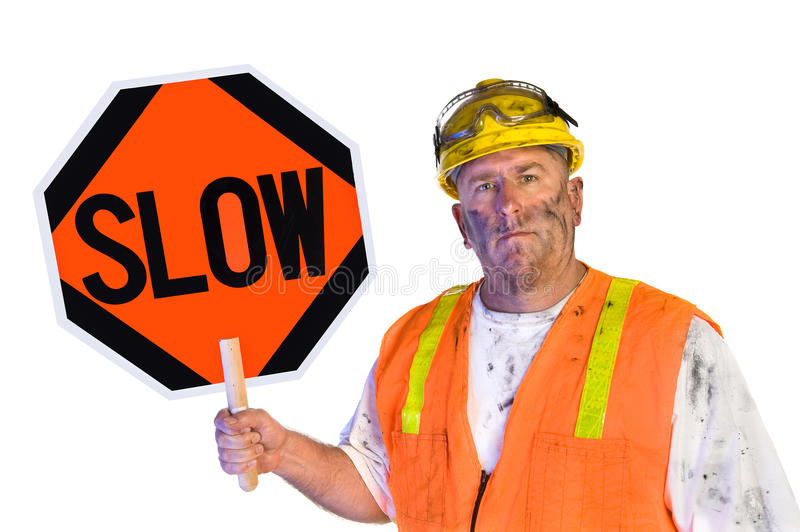 Construction worker holding a slow sign. A dirty, grungy, greasy utility construction worker with hard hat, orange vest and eye protection holds up a slow sign stock image