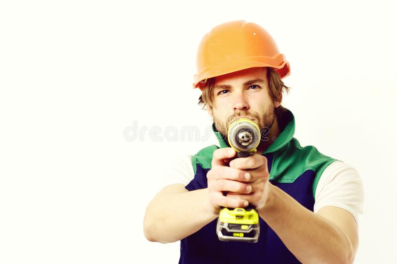 Construction worker holds yellow drill as gun. Builder with drill royalty free stock photo