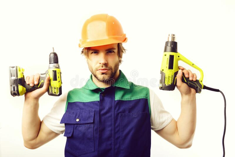 Construction worker holds yellow drilling tools. Man with confident face royalty free stock photos