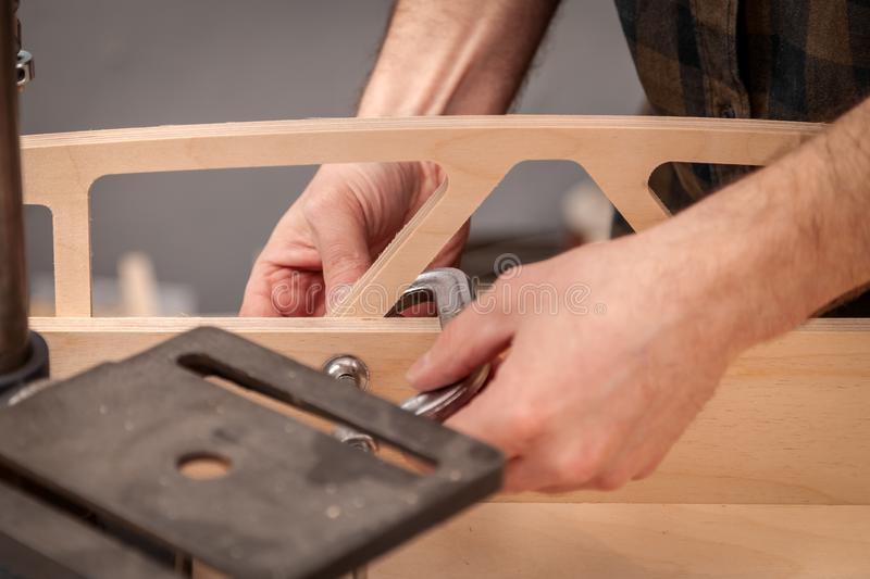 Construction Worker. Home repair concepts, close up. Handicraft Carpentry. Cabinet-maker hands tightens the nuts  on wooden board with a clamp on the working stock image