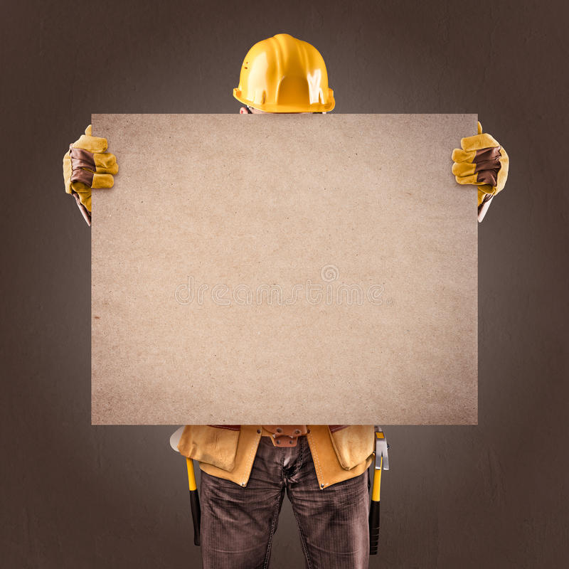 construction worker with information posters on a brown background stock photography