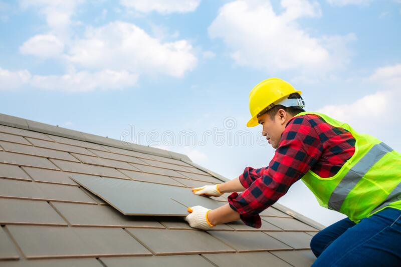 Construction worker install Roof repair, Fixing roof tiles on house with blue sky in safety kits for safety royalty free stock photography