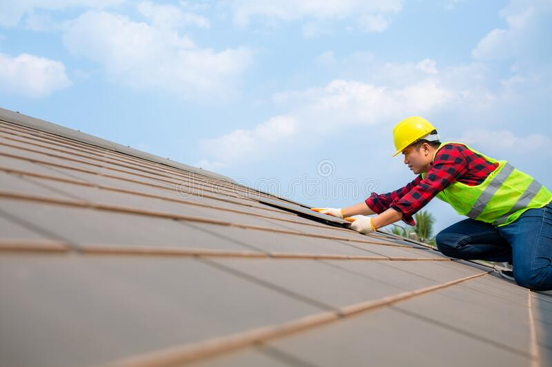 Construction worker install Roof repair, Fixing roof tiles on house with blue sky in safety kits for safety royalty free stock photo