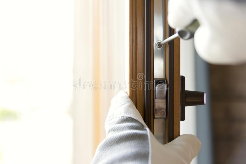 Construction worker installing window in house. Handyman fixing the window with screwdriver stock image
