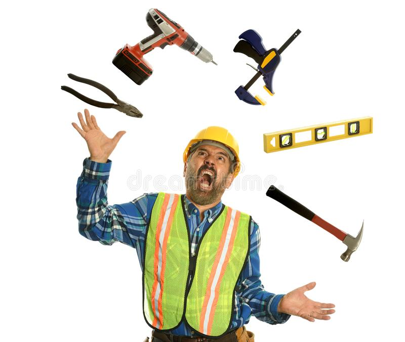 Construction worker juggling with tools. And showing stress isolated on a white background royalty free stock photo