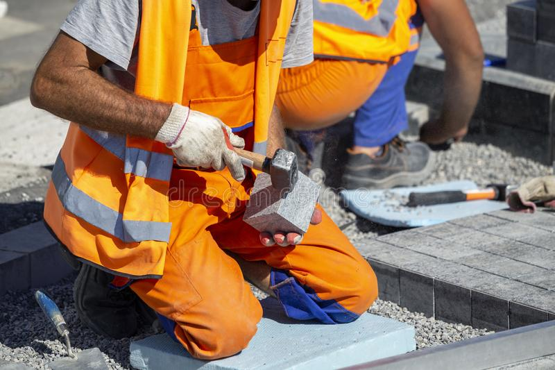 Construction worker on knees laying paving bricks outdoor royalty free stock photo