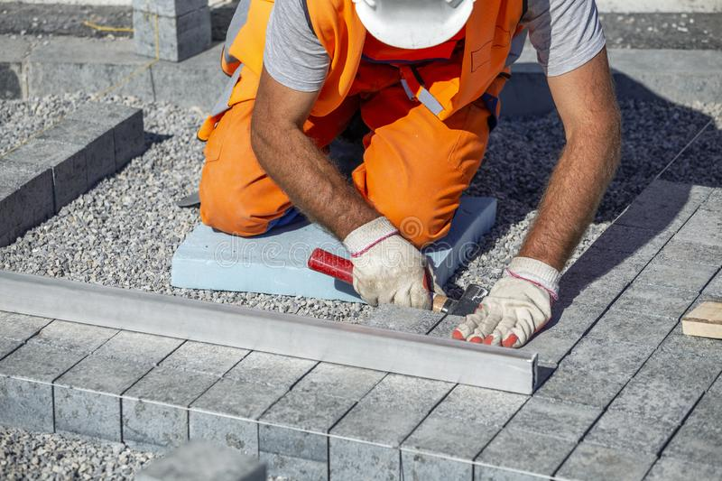 Construction worker on knees leveling paving bricks royalty free stock photography