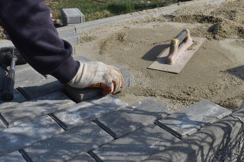 Construction worker are laying concrete pavement stone for footpath work at the construction site. Paving stone worker is putting stock photos