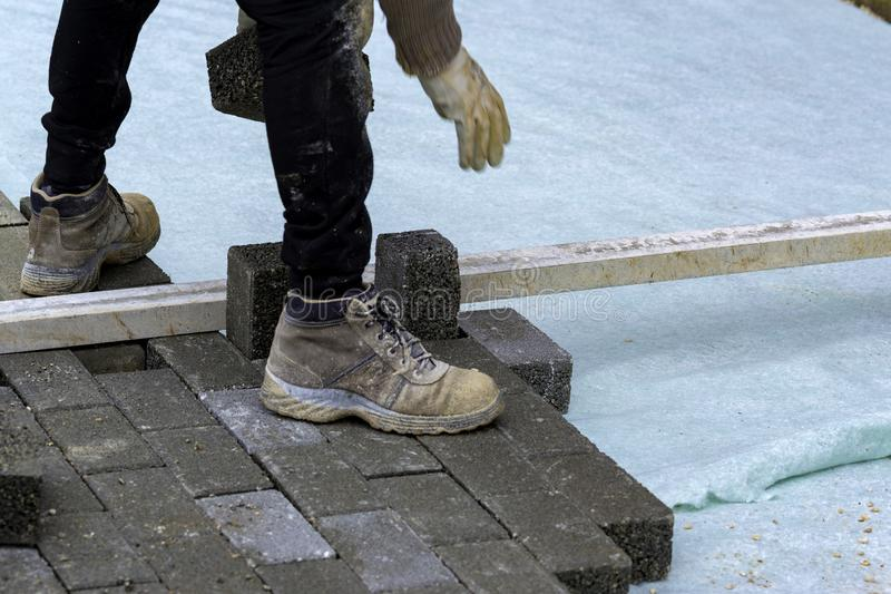 Construction worker laying interlocking paving concrete. Onto sheet nonwoven bedding sand and fitting them into place royalty free stock photography