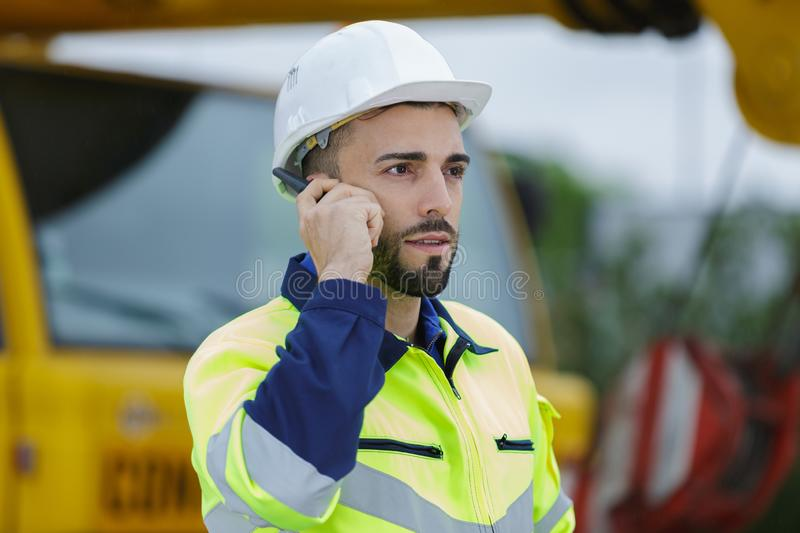 Construction worker listening to instructions via walkie-talkie royalty free stock photo